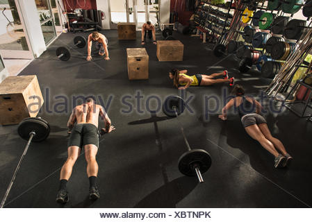Bodybuilder doing push ups in gym - Stock Photo