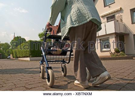old Germany Europe woman walking car person model release pensioner person retiree wheeled walker Salzkotten boss senior - Stock Photo