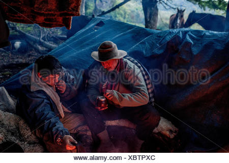 Bagualeros, cowboys who capture feral livestock, drink mate tea while camping. - Stock Photo