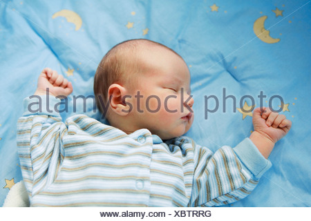 Baby sleeping on comforter - Stock Photo