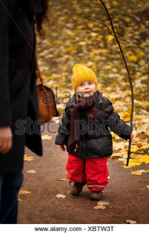 Young girl on walk wearing winter clothes, holding stick - Stock Photo