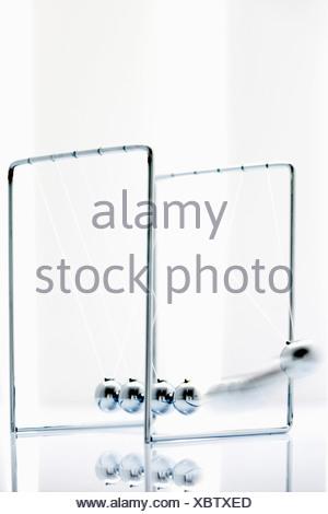 Newtons cradle on white background, close up - Stock Photo