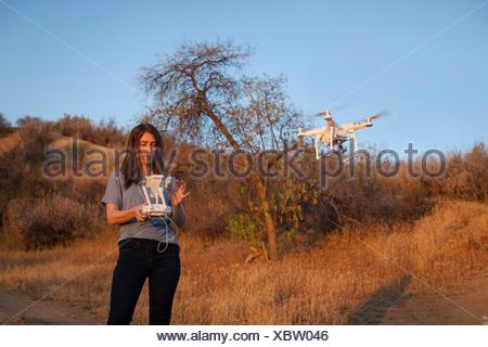 Female commercial operator on scrubland flying drone, looking down, Santa Clarita, California, USA - Stock Photo