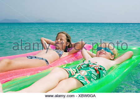 Young boy and young girl floating on inflatable rafts in the water smiling. - Stock Photo
