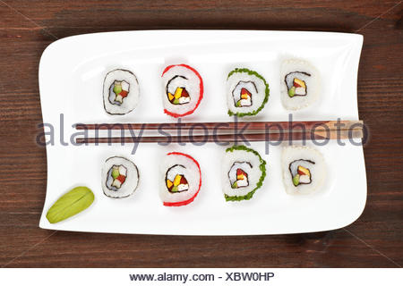 Maki sushi on white plate with chopsticks. - Stock Photo