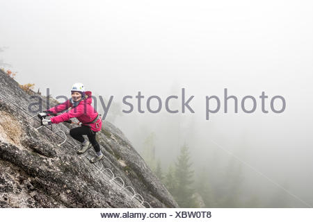 A women smiles with excitement as she climbs up the metal rungs of a Via Ferrata in Squamish. - Stock Photo