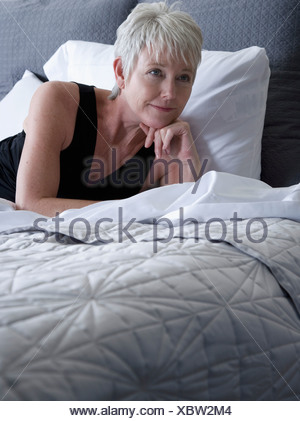 Portrait of smiling mature woman lying on bed - Stock Photo