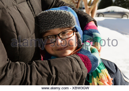 Mother hugging son wearing winter hat and glasses - Stock Photo