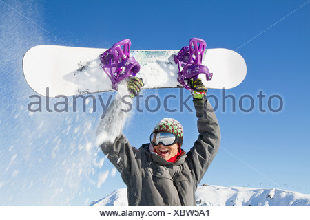 Young man holding his snowboard above his head - Stock Photo