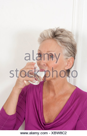 Older woman drinking glass of water - Stock Photo