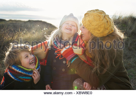 Mid adult woman in sand dunes with son and daughter wrapped in blanket - Stock Photo