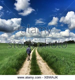 Rear View Of Man Walking On Dirt Road - Stock Photo