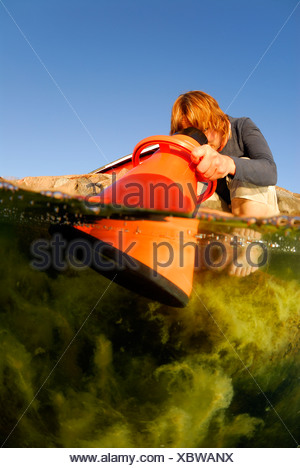 Woman looking through optical equipment into water - Stock Photo