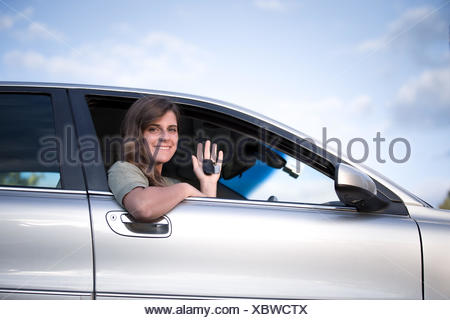 Teenage girl sitting in a car holding up  keys to new car - Stock Photo