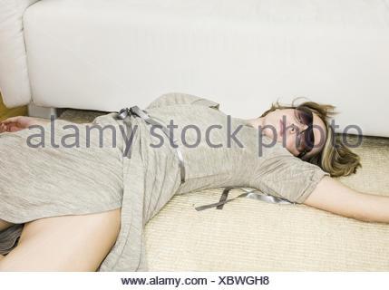 Frau liegt schlafend vor Sofa auf dem Boden (model-released) - Stock Photo