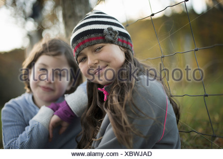 Two young girls side by side outdoors on a farm Leaning on a fence post - Stock Photo
