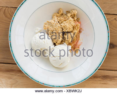 Traditional british apple crumble pie in dish with ice cream - Stock Photo