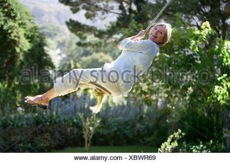 Senior woman swinging on garden rope swing smiling side view portrait - Stock Photo
