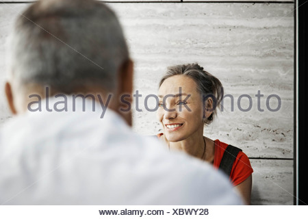 Woman smiling, man shot from behind - Stock Photo