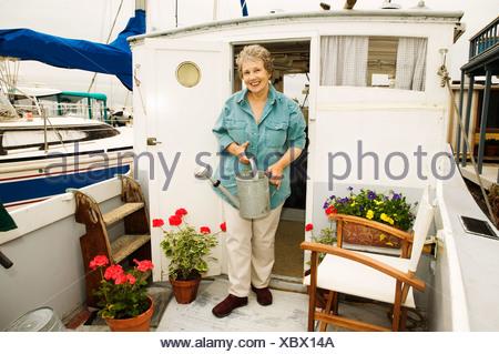 Woman on houseboat watering plants - Stock Photo