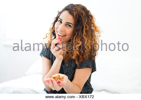 Woman eating almonds - Stock Photo
