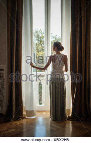 Elegant young woman looking out of sitting room windows - Stock Photo