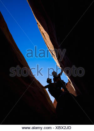 Adventurers exploring a desert slot canyon; Hanksville, Utah, United States of America