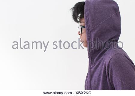 Studio profile portrait of young woman wearing hoody
