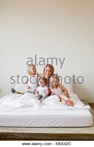 Portrait of mid adult woman in bed with three daughters - Stock Photo