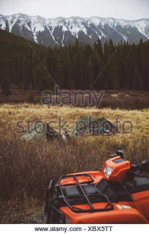 Quadbike and tents at campground in remote field below mountains - Stock Photo