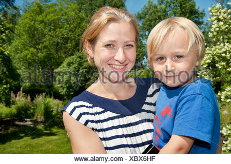 Sweden, Ostergotland, Vikbolandet, Portrait of mother with son (2-3) in park - Stock Photo
