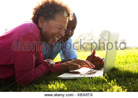 Senior couple lying in park using laptop - Stock Photo
