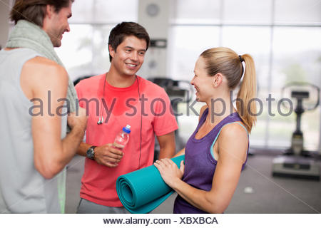Woman with yoga mat talking to men in gymnasium - Stock Photo