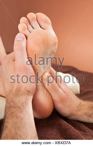 Closeup of male therapist giving foot massage to female customer at beauty spa - Stock Photo