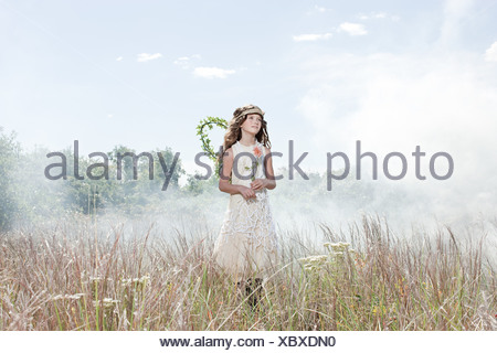 Girl dressed as fairy in field with flower - Stock Photo