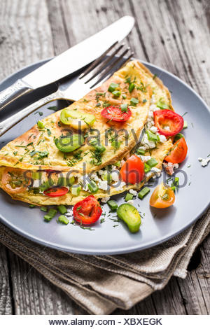 Omelette with vegetables and herbs on a plate - Stock Photo
