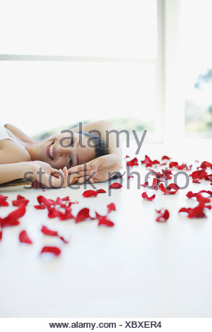 Smiling woman laying on floor with flower petals - Stock Photo