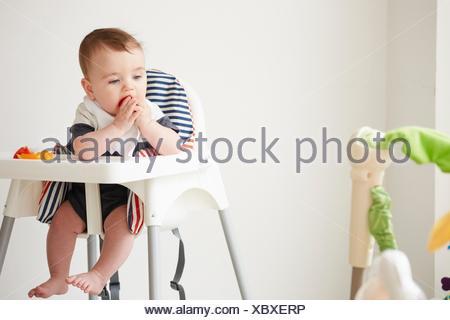 Baby boy feeding himself in baby chair - Stock Photo