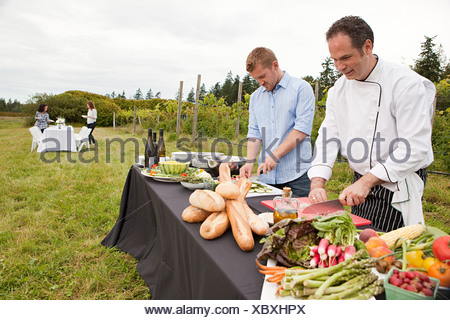 Men preparing food for dinner party in field - Stock Photo