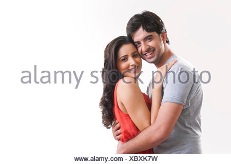 Portrait of happy young couple embracing against white background - Stock Photo