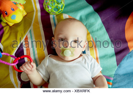 Baby boy lying on blanket sucking pacifier and playing with toys - Stock Photo