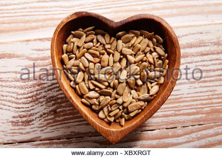 Sunflower seeds in a wooden heart shape bowl on wood board. - Stock Photo