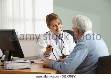 Doctor taking senior mans blood pressure - Stock Photo