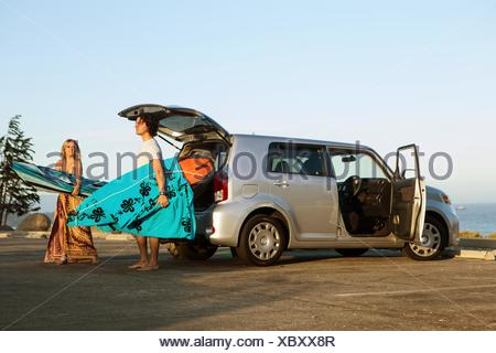 Couple taking surfboards from boot of car - Stock Photo