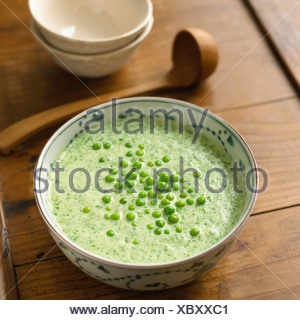 Chilled lettuce soup in a bowl with peas on top