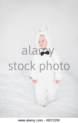 Girl wearing rabbit costume standing on bed - Stock Photo