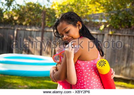 Two girls hugging in garden - Stock Photo