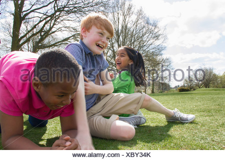 Two boys and a girl playing in field - Stock Photo