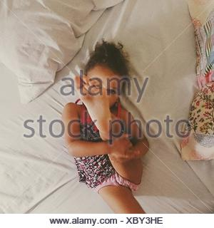 High Angle View Of Girl With Feet Up While Relaxing On Bed - Stock Photo