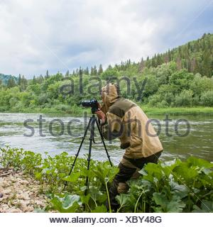 Male photographer photographing rural river - Stock Photo